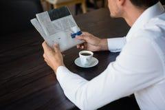 Средний раздел газеты чтения бизнесмена пока имеющ кофе на таблице Стоковые Фото