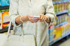 Средний раздел женщины используя smartphone Стоковые Изображения RF