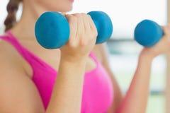 Средний раздел женщины работая с гантелями в студии фитнеса Стоковая Фотография