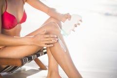 Средний-раздел женщины сидя на кресле и прикладывая лосьон солнцезащитного крема Стоковое Изображение