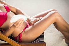 Средний-раздел женщины сидя на кресле и прикладывая лосьон солнцезащитного крема Стоковые Фото