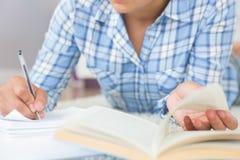 Средний раздел молодой студентки делая назначения пока лежащ на поле Стоковые Изображения RF
