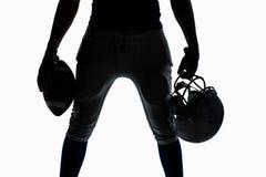 Средний раздел спортсмена силуэта держа шарик и шлем Стоковая Фотография