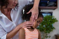 Средний-раздел физиотерапевта давая массаж шеи к пациенту девушки Стоковые Фото