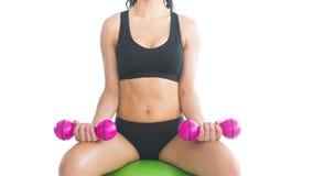 Средний раздел худенькой тренировки женщины пригонки при гантели сидя на шарике тренировки Стоковое Изображение RF