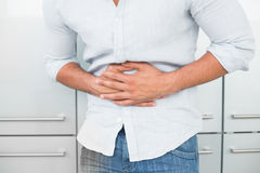 Средний раздел человека страдая от боли в животе Стоковое фото RF