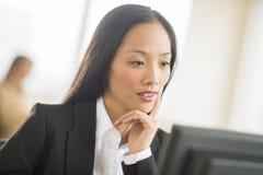 Средняя взрослая коммерсантка работая на компьютере в офисе Стоковые Изображения