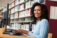 Средняя женщина времени работая на компьютере в библиотеке стоковое изображение rf