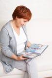 Средняя женщина смотря книгу фото Стоковое Фото