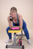 Средняя постаретая женщина сидя на стенде в спортзале Стоковое Фото