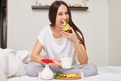 Средняя съемка женщины завтракая в кровати Стоковые Изображения RF