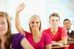 Средняя школа: Рука повышения студента с ответом Стоковые Изображения