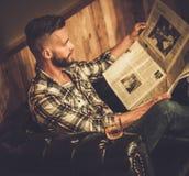 Средн-постаретая газета чтения битника в парикмахерской Стоковые Изображения RF