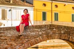 Средн-постаретая женщина на мосте в городке лагуны Стоковое Изображение RF