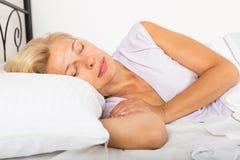Средн-постаретая женщина спать в кровати стоковая фотография