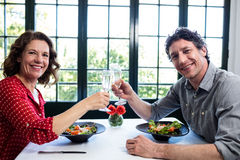 Средн-постаретые пары провозглашать каннелюры шампанского пока имеющ обед Стоковое Фото