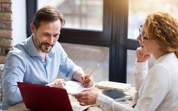 Средн-постаретые пары работая на компьтер-книжке и принимая примечания Стоковые Изображения