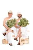 Средн-постаретые люди в костюмах русской сауны купая стоковые фото