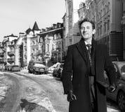 Средн-постаретый бизнесмен, в темном пальто, усмехаясь на камере, день, внешний Стоковые Фото