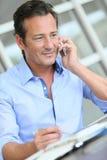Средн-постаретый бизнесмен делая контракты на телефоне Стоковые Фото