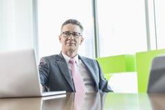 Средн-постаретый бизнесмен при компьтер-книжка сидя на столе переговоров Стоковые Изображения RF