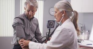 Средн-постаретый мужской пациент имея кровяное давление быть проверенным стоковые изображения rf
