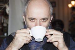 Средн-постаретый облыселый человек выпивая от белой чашки Стоковые Фотографии RF