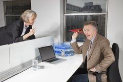 Средн-постаретый самолет бизнесмена бросая бумажный к женскому коллеге в офисе Стоковые Изображения