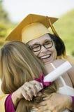 Средн-постаретый студент-выпускник обнимая дочь снаружи Стоковые Фотографии RF