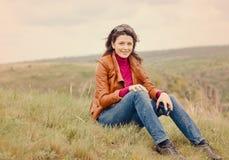 Средн-постаретый думать женщины сидя outdoors Стоковая Фотография RF