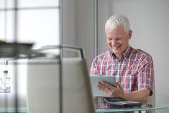 Средн-постаретый человек используя высокотехнологичный ПК таблетки Стоковые Изображения