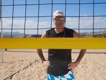Средн-постаретый человек смотрит через сеть волейбола стоковые фотографии rf