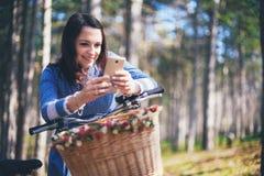 Средства массовой информации счастливой девушки наблюдая в умном телефоне сидя в улице около ее велосипеда Стоковые Изображения RF