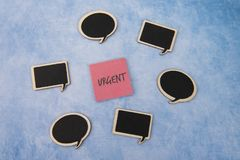 Срочное написанное на розовой бумаге примечания окруженной речью клокочет стоковое фото rf