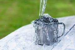 Стальная кружка с водой и брызги на белом деревянном столе на предпосылке природы Стоковое Изображение