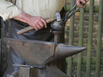 Стальная наковальня, поверх которой лежит горячий workpiece, рука процессов кузнеца workpiece с помощью молотка стоковая фотография rf