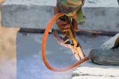Стальные пруты человека сварщика сваривая поддерживать precast бетонную стену, работника с незащищенным и unsafety стоковые фото