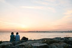Стамбул, 14-ое июня 2017: 2 друз сидят на побережье около моря, связывают и наслаждаются взгляд Bosphorus и Стоковое Фото