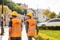 Стамбул, 16-ое июня 2017: 2 неизвестных люд в рабочей одежде - защитные шлемы и желтые жилеты идут вперед Стоковые Фотографии RF