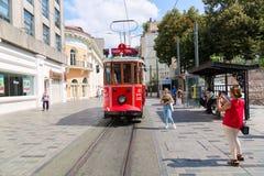 Стамбул, Турция - август 2018: Туристы маленьких девочек делая фото из ретро трамвая на улице Istiklal Красный трамвай Taksim-Tun стоковое изображение