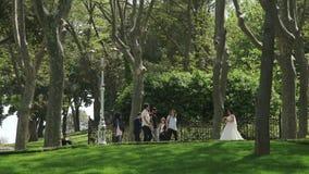 СТАМБУЛ, ТУРЦИЯ, 3-ЬЕ ИЮНЯ 2017: Groom фотографирует невеста в парке видеоматериал
