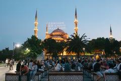 Стамбул, 16-ое июня 2017: Много людей исламского вероисповедания принимают еду на квадрате Sultanahmet рядом с голубой мечетью Стоковое Изображение