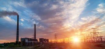 Станции и линии электропередач тепловой мощности во время захода солнца стоковое фото rf