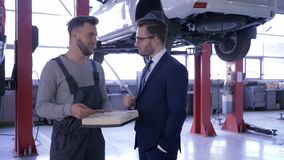 Станция обслуживания, mechanician с воздушным фильтром в руке связывает к клиенту на предпосылке автомобиля на гидравлическом сток-видео