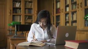 Старательно сочинительство биолога студентки на таблице с книгой и компьтер-книжкой в библиотеке сток-видео