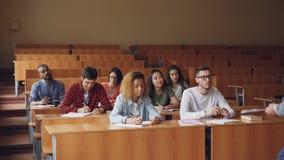 Старательно студенты пишут делающ примечания в тетрадях сидя на лекции на коллеже пока учитель говорит стоять сток-видео