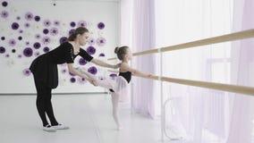 Старательный меньший студент балета в bodysuit имеет индивидуальный урок балета с профессиональным учителем уча сток-видео