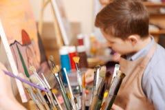 Старательно мальчик имея художественный класс в школе стоковые изображения