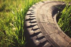 Старая автошина в траве стоковые изображения