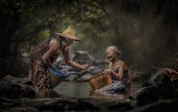 Старая азиатская женщина работая в каскаде Стоковые Изображения RF